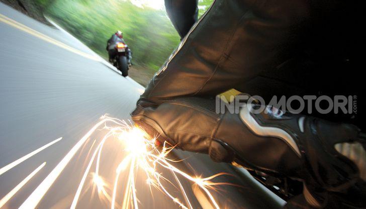 Pilota ginocchio a terra moto su strada